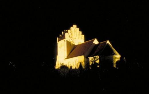 Belyst landsbykirke. Læg mærke til, hvordan især tårnet har fået et skråt snit af lyset. Fot.: P.T.Aldrich.